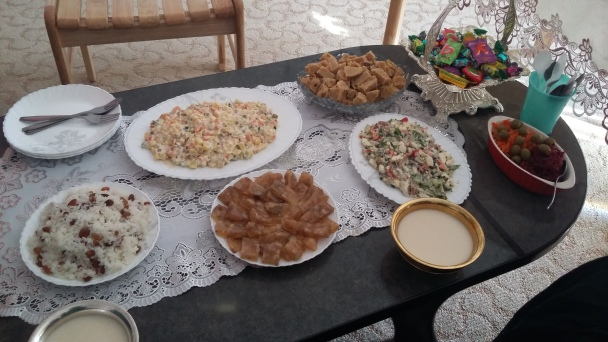 Tsagaan Sar spread! On the table are several kinds of salads, rice with raisins, cow's foot jelly, candies, and milk tea (served in metal bowls).